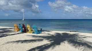 Colorful chairs at palm beach Aruba with a sailboat at the background