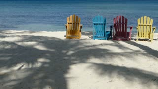 Colorful chairs at palm beach Aruba with palm tree reflection at the beach