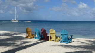 Colorful chairs at palm beach Aruba with speedboat passing by