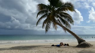 Couple laying under a palm tree a Tulum beach in Yucatan, Mexico