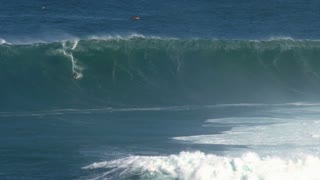 Crazy surfer at a massive wave surfing break called Jaws in Peʻahi at the north shore of the island of Maui, Hawaii