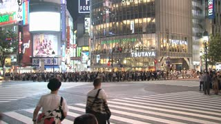 Crowded intersection outside Shibuya Station at night.