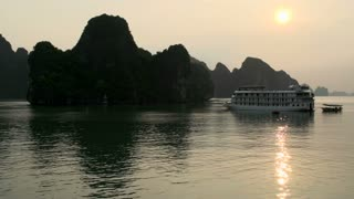 Cruise ship leaving in the morning one of the bays in Ha Long Bay