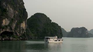 Cruise ship sailing away in Ha Long Bay