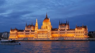 Cruise ships and ferries with the Hungarian Parliament Building in the evening at the Danube river in Budapest, Hungary