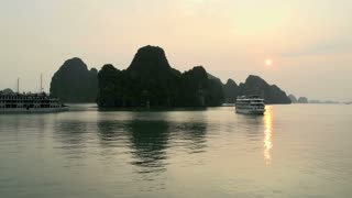 Cruise ships passing by the mountains in Ha Long Bay