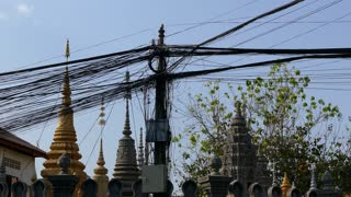 Electricity wires with temple at the background downtown Phnom Penh Cambodia