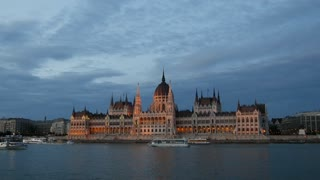 Evening time lapse from cruise ships and ferries with the Hungarian Parliament Building at the Danube river in Budapest, Hungary