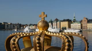 Focus pull from golden Royal Crown on the Skeppsholmsbron bridge to Gamla stan in Stockholm, Sweden