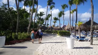 Following tourist walking at palm beach on Aruba