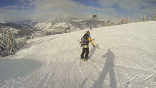 Follwing snowboarder while skiing down hill
