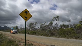 Funky camper van drives by a Kangaroo and Emu Sign at the The Stirling Ranges, Western Australia