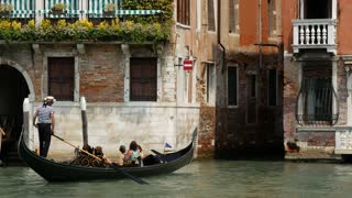 Gondola going in to a narrow canal next to a traditional house in Venice Italy
