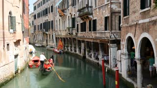 Gondola in a canal and Venetian flag in Venice Italy