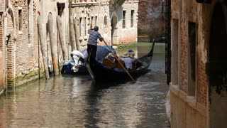 Gondola in a narrow canal ging around the corner in Venice Italy