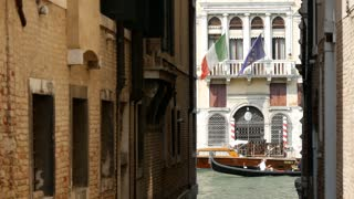 Gondola passing by under Italian and European flag in Venice Italy