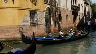 Gondola witgh tourists in a canal in Venice Italy