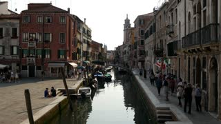 Group of tourists walking next to the canals in Venice Italy