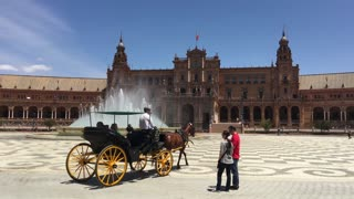 Horse and carriage driving around the Fountain at the Plaza de Espana in Seville Spain
