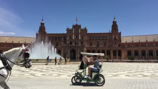 Horse and carriages driving around the Fountain at the Plaza de Espana in Seville Spain