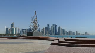 Man cycling at the Corniche boulevard with a statue and the Doha skyline in the background