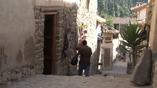 Man entering a house in the old streets of Ollantaytambo Peru