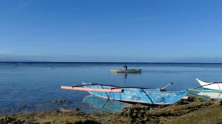 Man leaving with a catamaran boat in the morning at Balicasag Island in Bohol the Philippines