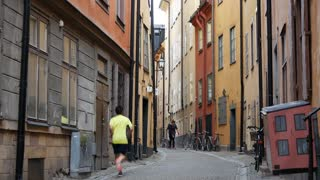 Man running in a street in Gamla Stan Old town Stockholm Sweden