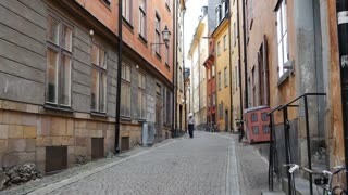 Man walking in a street in Gamla Stan Old town Stockholm Sweden