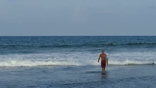 Man walks with a surferboard in to the water at Arugam Bay beach Sri Lanka