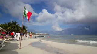 Mexican flag and people at the beach in Playa del Carmen Yucatan, Mexico