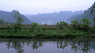 Mountains and farm land with reflection in a lake in Mai Châu