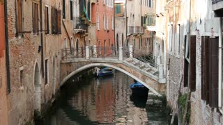 Narrow canal with a bridge and houses in Venice Italy