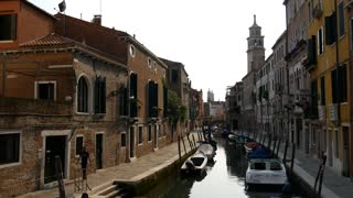 Narrow canal with houses and boats in Venice Italy