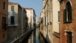 Narrow canal with houses in Venice Italy
