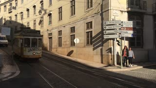 Pan following a Yellow tram passing by in the old town of Lisbon Portugal