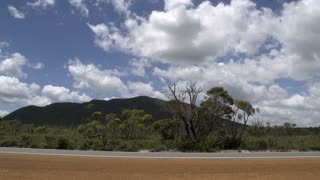 Pan from the road with cars passing by  through the Stirling Ranges, Western Australia