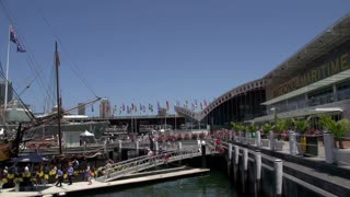 Pan of Darling harbour national maritime museum in Sydney with Sydney tower and skyline at the background