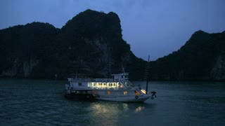 Passing by a cruise ship in the evening in Ha Long Bay