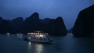 Passing by cruise ships in the evening in Ha Long Bay
