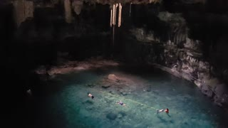People swimming in a cenote in Yucatan, Mexico