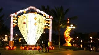 People walk around a big lantern next to the thu bon river side in the old town of Hoi An Vietnam