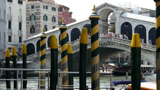Pier with yellow green poles with Ponte di Rialto at the background in Venice Italy