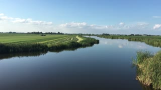 Quiet lake with a farmer working at the land in Friesland The Netherlands