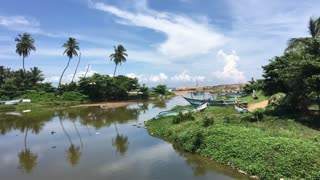 River with fishing boats and palmtree reflection in Sri Lanka