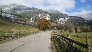 Road and snowy mountain landscape next to the river Dorna in Romania