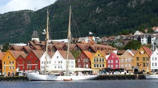 Sailboat in front of Bryggen (the dock) Tyskebryggen buildings at the Vagen harbour in Bergen, Norway