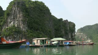 Sailing through floating fishing village in Ha Long Bay