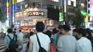 Shinjuku district people crossing a busy pedestrian end of day Tokyo, Japan
