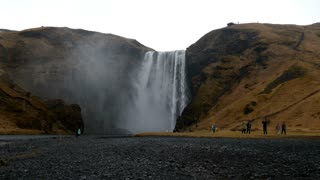 Skógafoss waterfall in the winter with tourism and rain